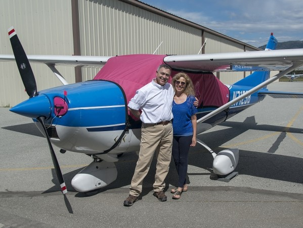 Bruce and Heather standing next to their 1969 Cessna 182M: